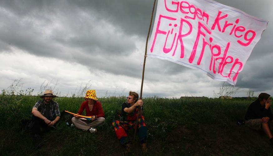 Aktivisten halten eine selbstgemalte Fahne mit der Aufschrift: Gegen Krieg Für Frieden © REUTERS/Kai Pfaffenbach