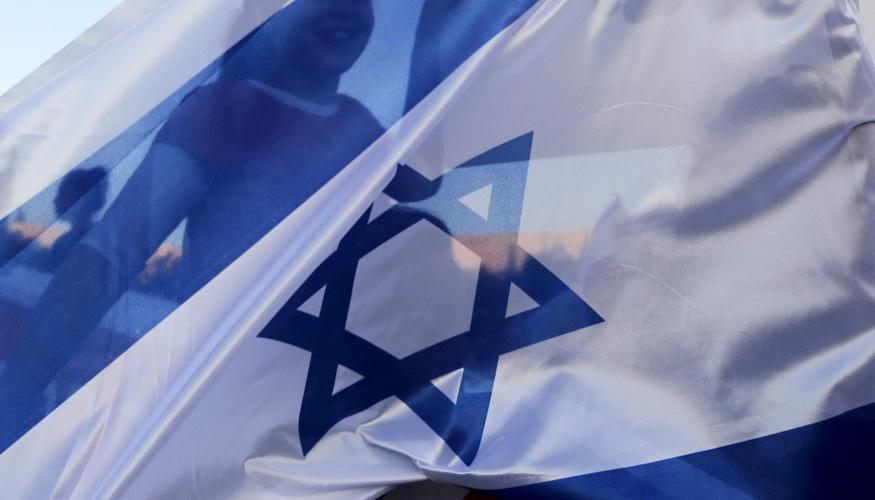 Durch eine Israel-Fahne scheint die Silhouette eines Mädchens © REUTERS/Ammar Awad