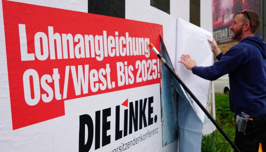Ein Arbeiter bringt am 2. Mai 2019 in Leipzig eine Großfläche an mit der Aufschrift: »1:1 - Lohnangleichung Ost/West. Bis 2025!« © Olaf Krostiz