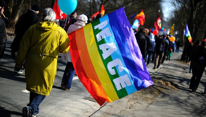 Eine Teilnehmerin beim Ostermarsch Rhein-Ruhr am 1. April 2013 in Bochum trägt eine Fahne mit der Aufschrift Peace © dpa/Marius Becker