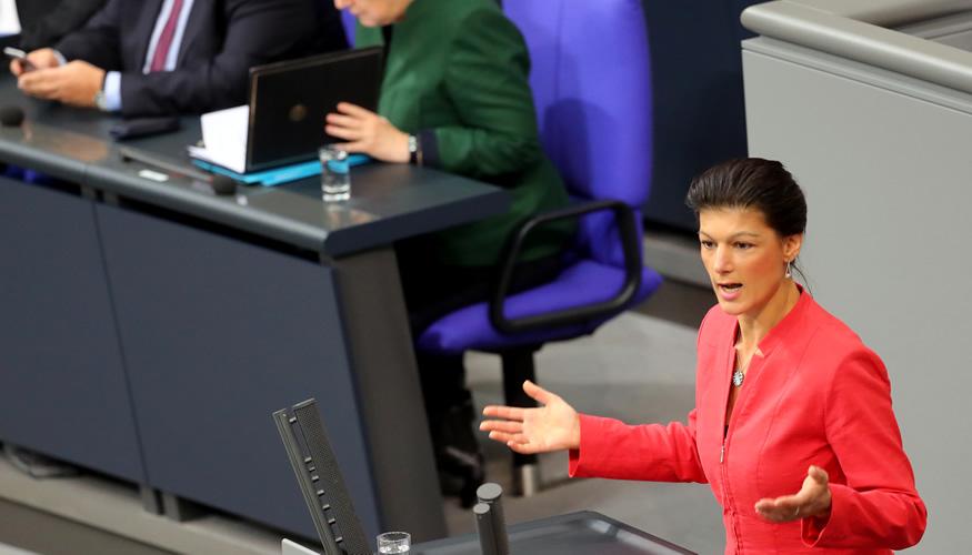 Sahra Wagenknecht am Rednerpult des Bundestages, dahinter Kanzlerin Merkel auf der Reigerungsbank © dpa