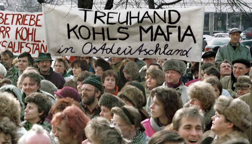 Bei einer Demonstration gegen die Treuhandanstalt im Jahre 1991 am Alexanderplatz in Berlin halten Teilnehmer ein Transparent mit der AUfschrift: Treuhand Kohls Mafia in Ostdeutschland © dpa/Paul Glaser
