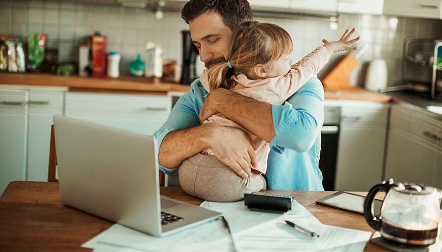Junger Vater mit seiner Tochter am Küchentisch, auf dem ein Taschenrechner liegt